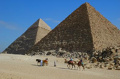 The image is a photograph of people riding camels in front of two pyramids in Egypt.