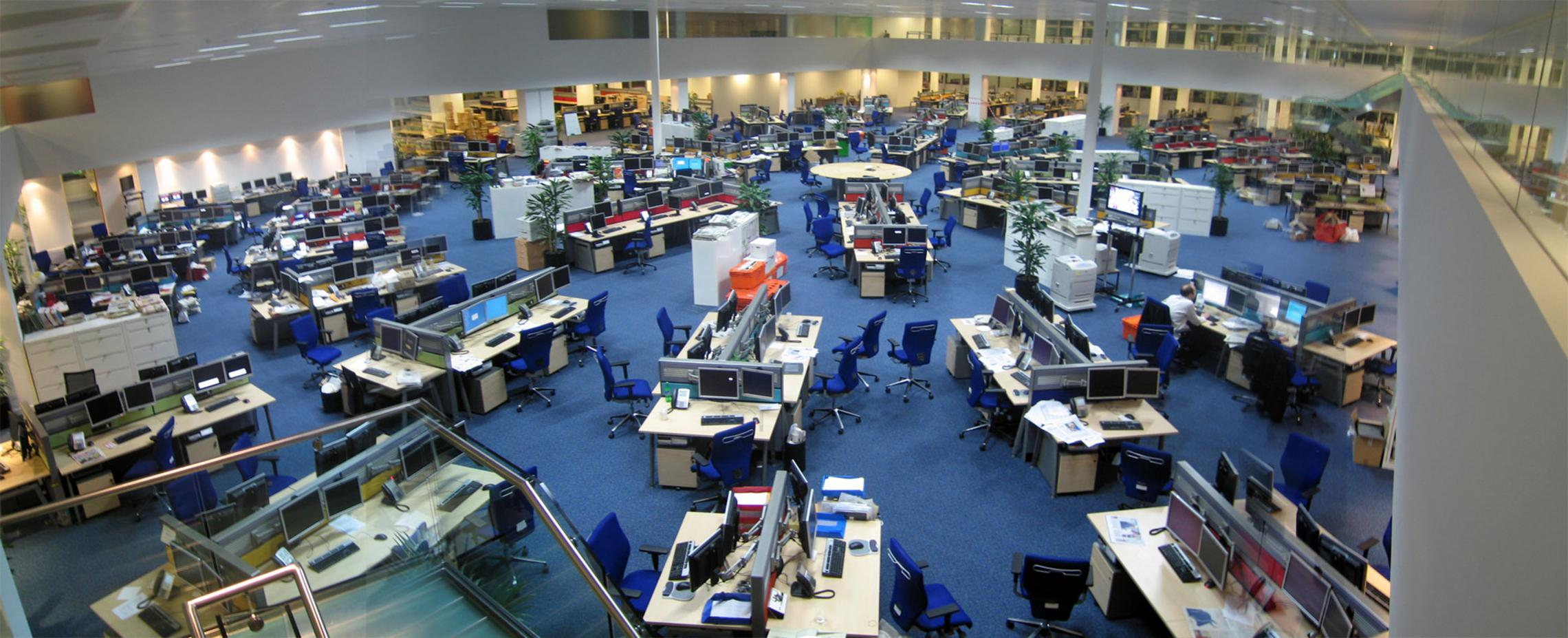 This photo shows a large open news room with enough space to seat about 200 employees.