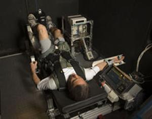 An astronaut is strapped into a G-Force simulator.