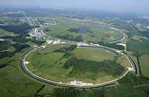 An aerial view of the Fermi National Accelerator Laboratory is shown.