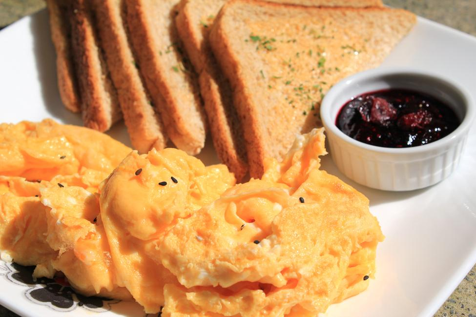 This is a photo of a plate with a large pile of eggs in the foreground and six slices of toast in the background. There is a small dish of red jam sitting near the toast on the plate.