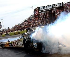 Smoke is coming from the tires of a race car as the car accelerates at the beginning of a drag race.