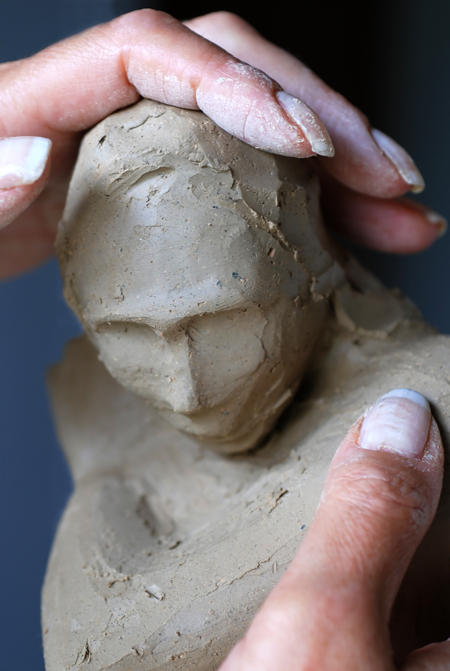 Image of the hands of a sculptor working with clay