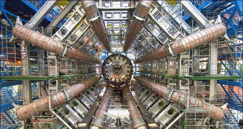 The photograph shows a series of tubes and structural elements that make up the Large Hadron Collider. The five staircases on the sides of the collider show the very large size of the experimental device.
