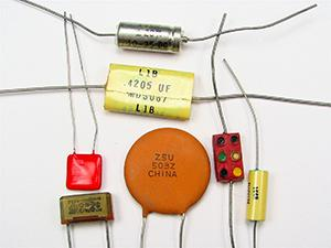 This is a photograph showing seven small capacitors, of varying shapes and colors, usually found in electronic circuits.
