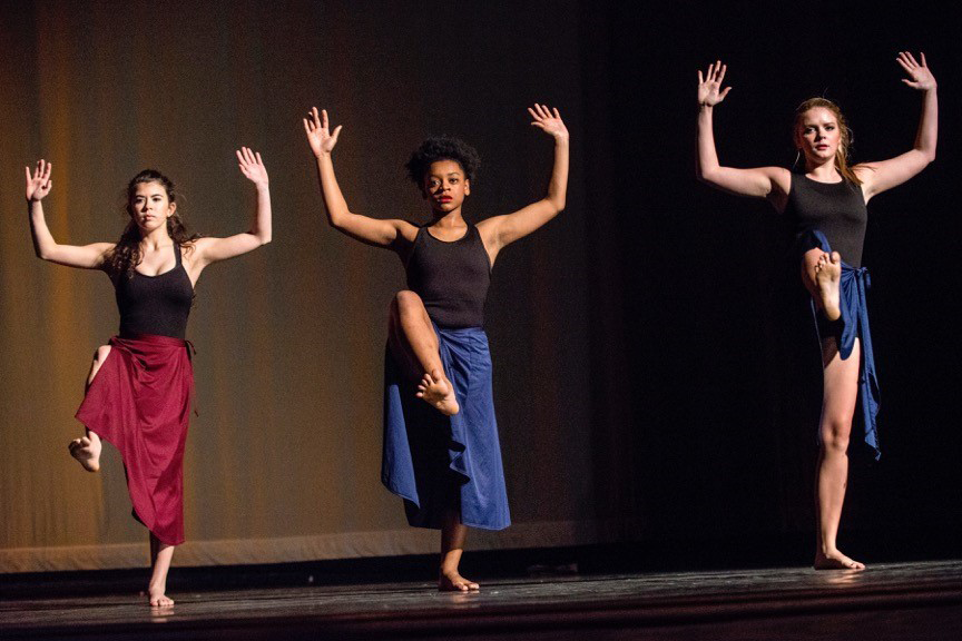 Image of three dancers holding a position on stage