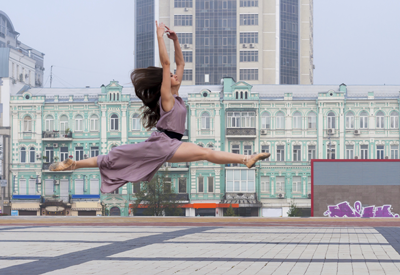 Image of dancer leaping with city skyline in the background