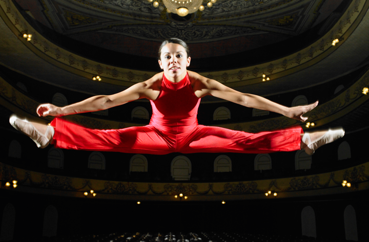 Image of dancer on stage performing a jump