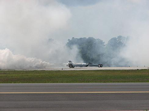 A photograph of a United States Air Force jet car is shown speeding down a track. Smoke is billowing from the back end.