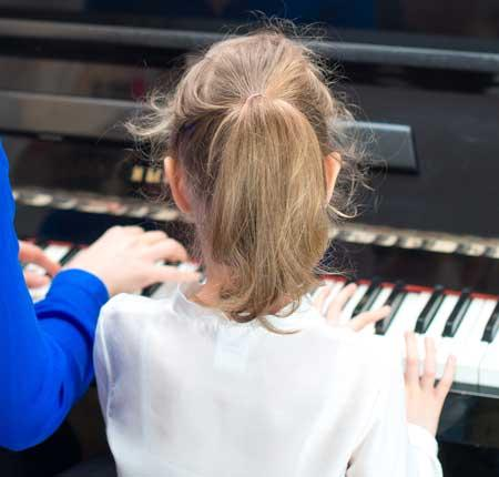 Image of girl playing piano next to an instructor