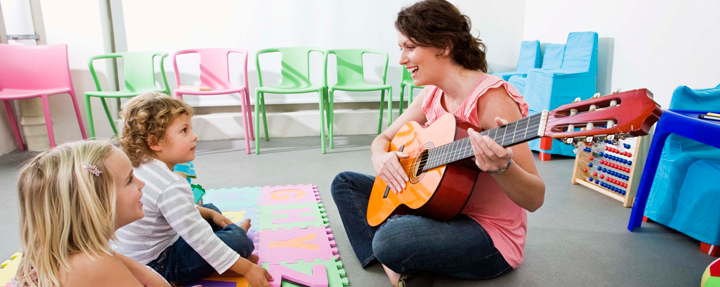 Image of two young students listening to teacher with guitar