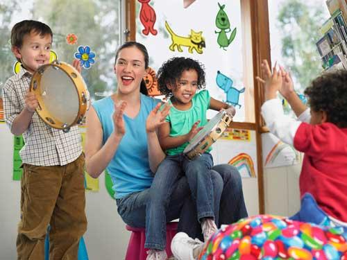 Image of children with percussion instruments in a classroom with their teacher
