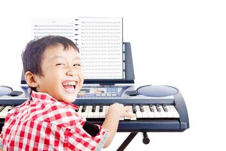 Image of boy playing the keyboard with sheet music in front of him