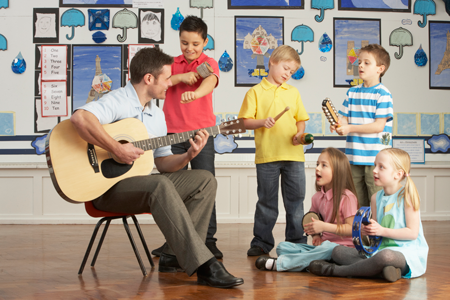 Image teacher with guitar in front of elementary students with instruments