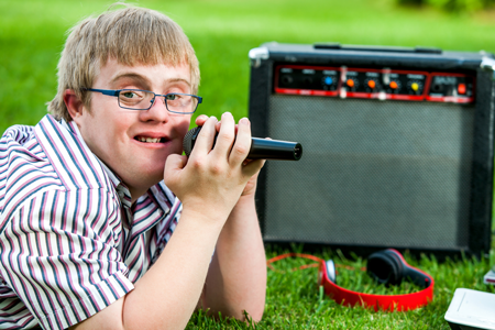 Image of a special education student with microphone and speaker