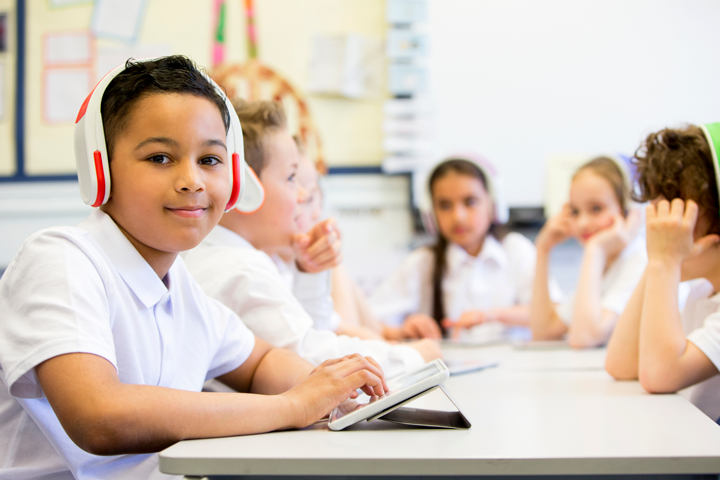 Image of boy with headphones and a tablet with other students in the background