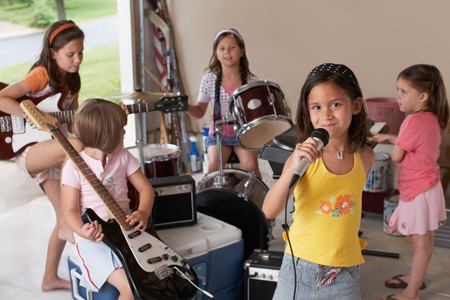 Image of young girls playing instruments in a garage