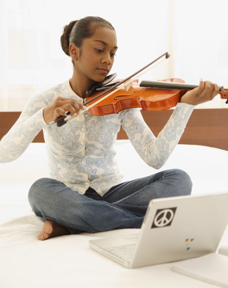 Image of a girl playing the violin in front of her laptop