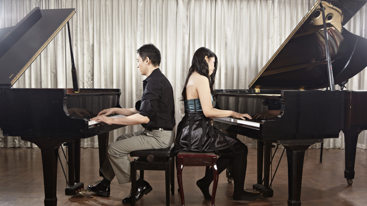 Image of two students playing pianos