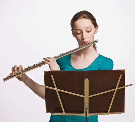 Image of a student playing the flute and reading music from a music stand