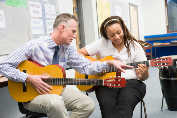 Image of teacher and student playing guitar