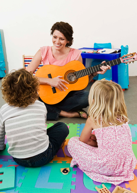 Image of students sitting in front of teacher with guitar