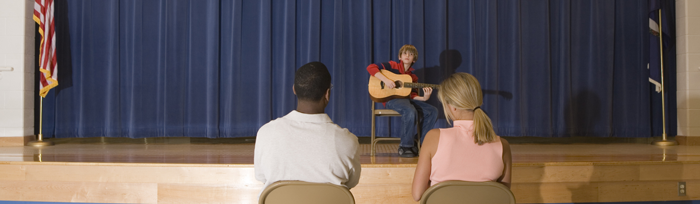Image of boy with guitar performing on stage in front of two adults in the audience