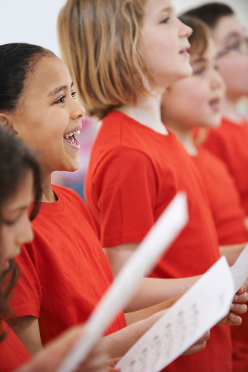 Image of students singing with sheet music