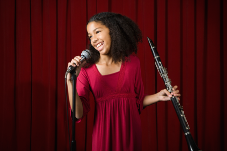 Image of girl on stage with clarinet and microphone