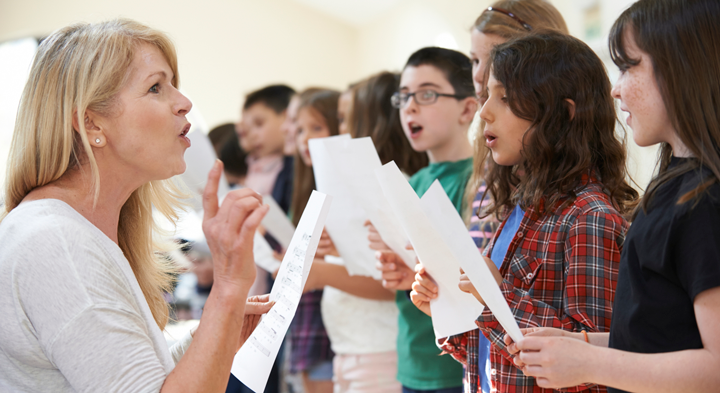 Image of choir teacher with a group of students singing with sheet music