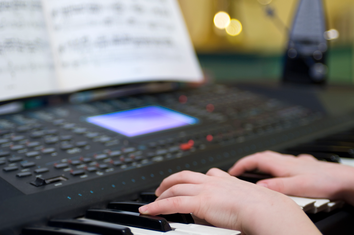 Image of a person playing the keyboard with sheet music and a metronome in the background