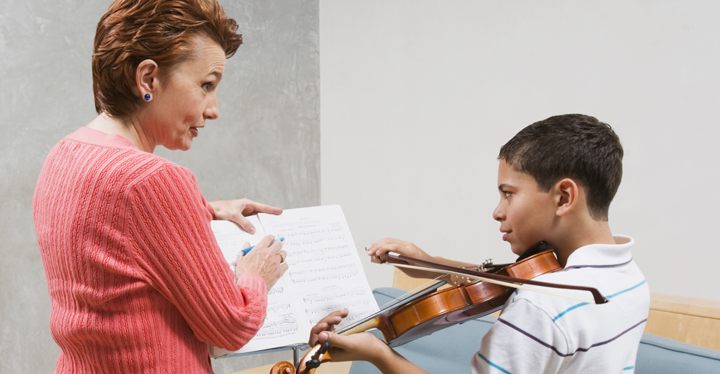 Image of a student playing the violin with guidance from his instructor