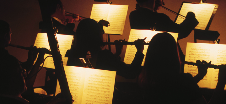 Image of classical musicians with illuminated sheet music