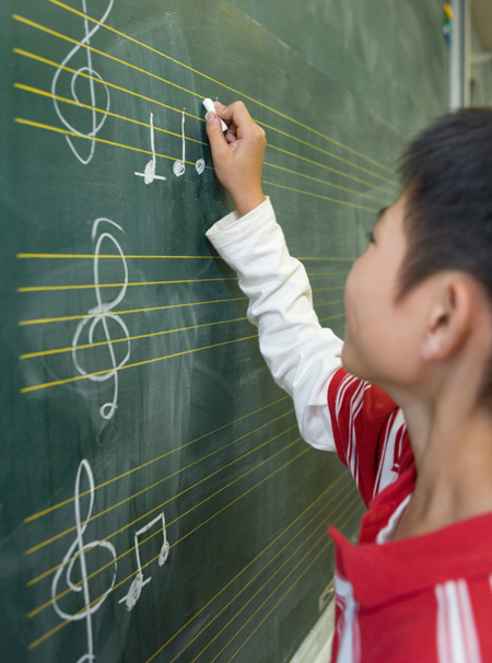 Image of student writing music on a chalkboard