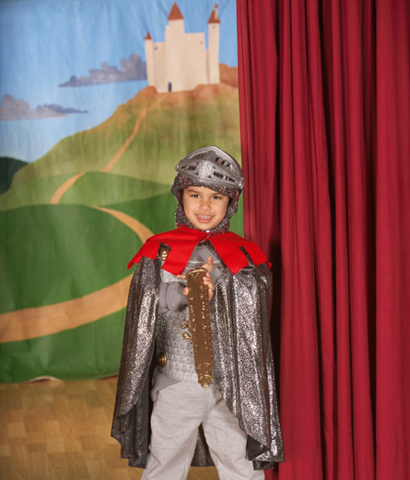 Image of young boy in costume on stage with painted backdrop