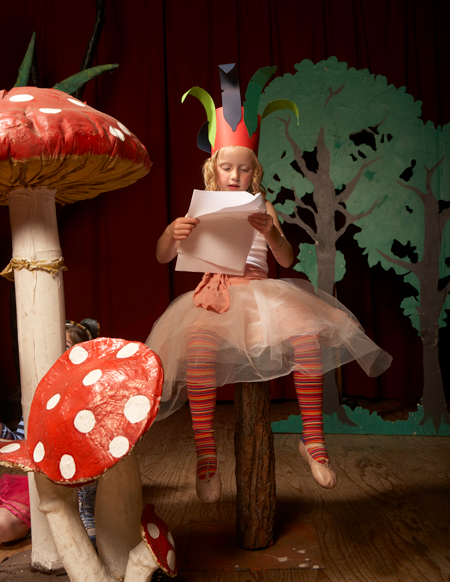 Image of girl reading a script in costume on stage