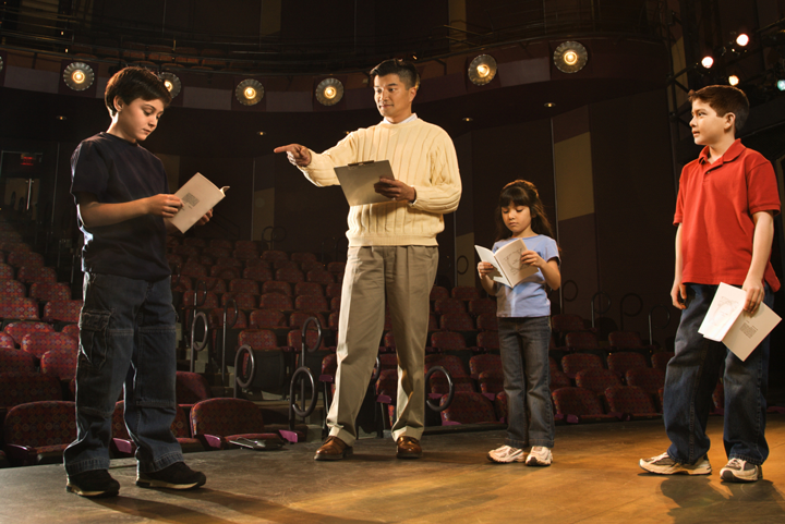 Image of a group of students on stage with their teacher