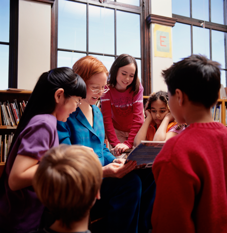 Image of teacher reading a story to a group of students