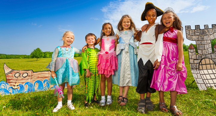 Group of young children in costumes in front of a set