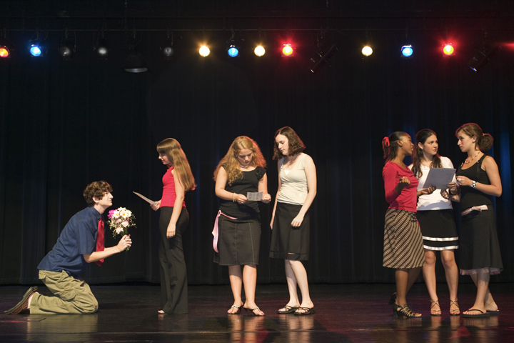 Students on stage reading lines