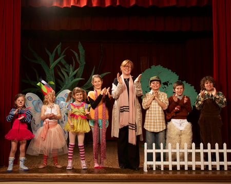 Image of elementary students and teacher on stage in front of set