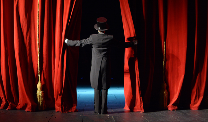 Image of child in costume on stage looking out into the audience from behind a red curtain