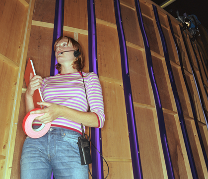 Image of woman backstage with clipboard, tape, and headset