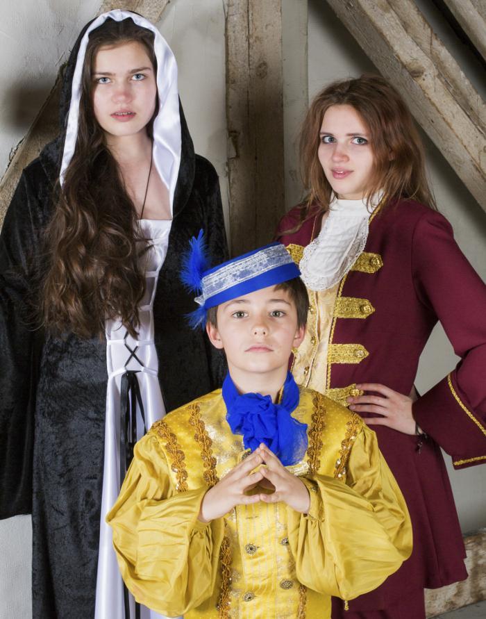 Three children dressed in period costumes