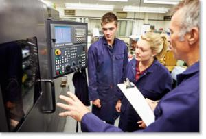 Male describing electronic equipment to a male and a female apprentice