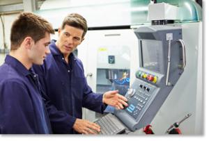 Manufacturing worker demonstrating use of automation equipment to a student