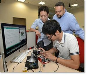 Male student soldering electronic equipment as instructor looks on