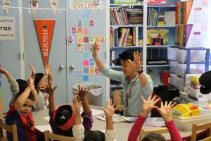 teacher and children in a classroom all holding their hands up