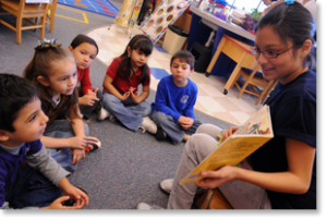 A high school student reading to a group of young children