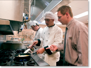 A teacher visits a WBL training site where student chefs are working